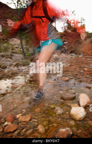 A woman trail running through a rocky stream in Nevada. - Stock Photo