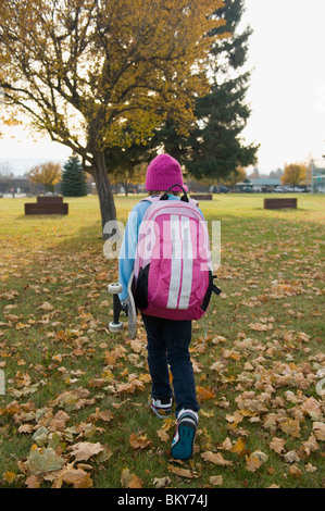 A young girl, carrying her skateboard, walks home from school on a fall day. - Stock Photo