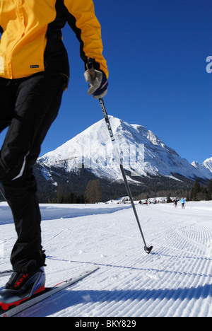 Woman cross-country skiing, Hohe Munde in background, Leutasch, Tyrol, Austria - Stock Photo