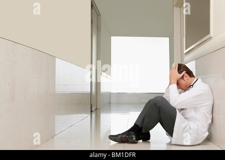 Doctor sitting on the floor looking depressed - Stock Photo