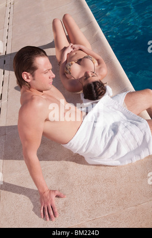 Couple resting by a swimming pool - Stock Photo