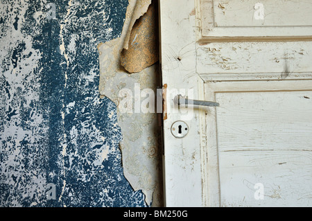 Torn vintage wallpaper peeling paint wall and wooden door in abandoned house. - Stock Photo