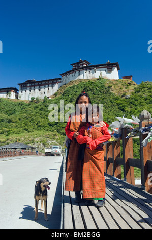 Two girls and dog on a bridge below Wangdue Phodrang Dzong, founded by the Zhabdrung in 1638, Bhutan - Stock Photo
