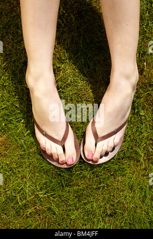 Close up of feet in flip flops - Stock Photo