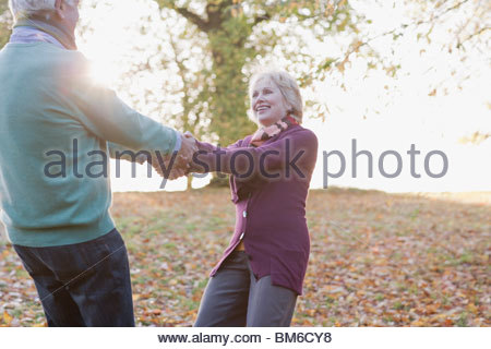 Senior couple holding hands outdoors in autumn - Stock Photo
