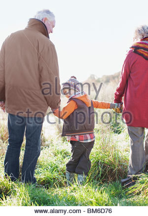 Grandparents holding hands with grandson - Stock Photo
