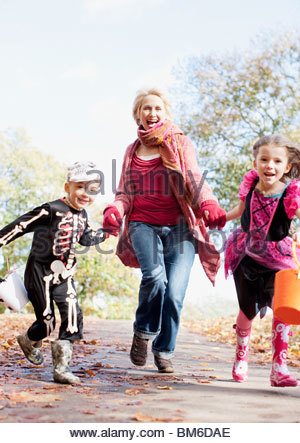 Grandmother running with grandchildren in Halloween costumes - Stock Photo