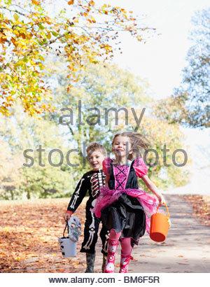 Children in Halloween costumes running in park - Stock Photo