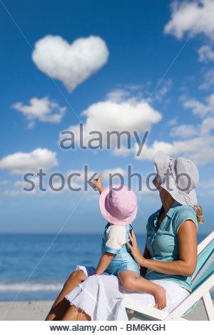 Mother and daughter looking at heart-shaped cloud in sky - Stock Photo