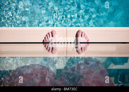 someones feet on the edge of a swimming pool against glass with a reflection making twin feet - Stockfoto