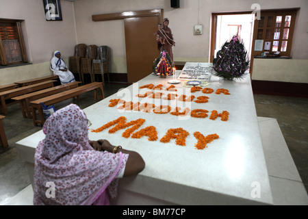 A num prays at the tomb of Mother Teresa at Mother House in Kolkata, formerly called Calcutta in West Bengal, India. - Stock Photo
