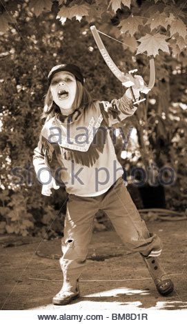 Full length little boy dressed as a Red Indian carrying his bow and arrows - Stock Photo