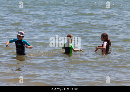 two boys and one girl pre teen in wet suits playing in the sea - Stock Photo