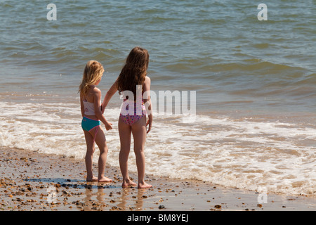 two young girls in swim suits standing together at edge of sea on beach looking out to sea - Stock Photo