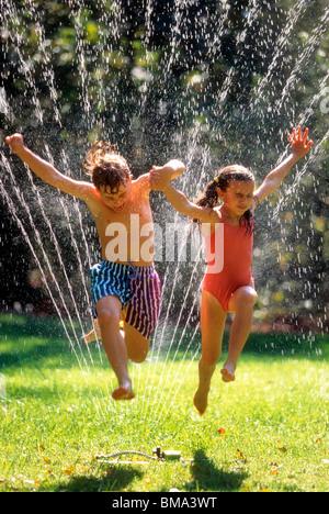 Kids jumping through lawn sprinkler. - Stock Photo