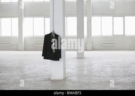 Suit jacket hangs on pillar in empty warehouse - Stock Photo