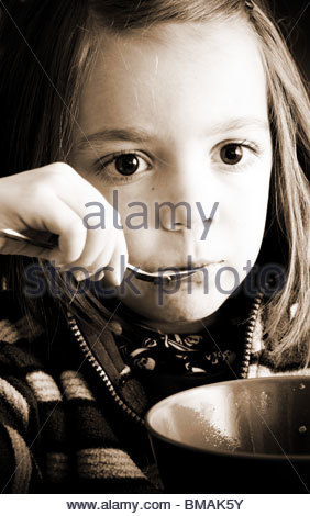 Four year old child eating food from a bowl holding a spoon - Stock Photo