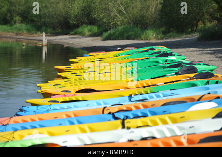 Many Colorful kayaks on the beach near lake - Stock Photo