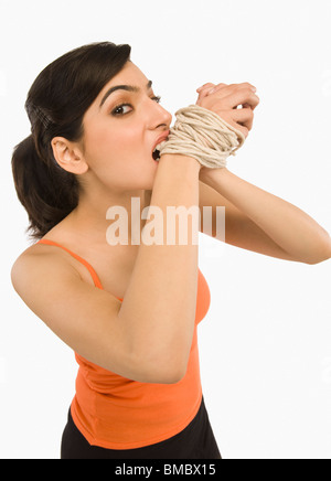 Woman's hands tied with a rope - Stock Photo