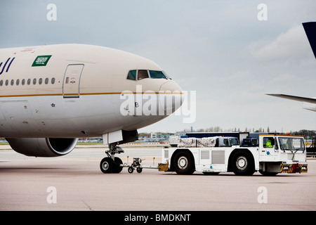 A commercial airliner being towed to its gate after landing at Heathrow airport London England - Stock Photo