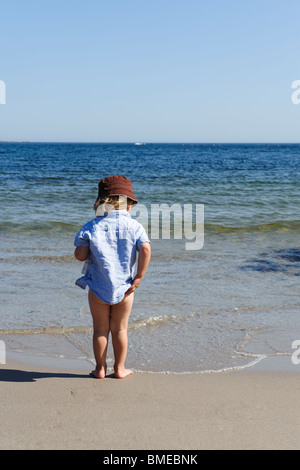 Boy standing at edge of sea - Stock Photo