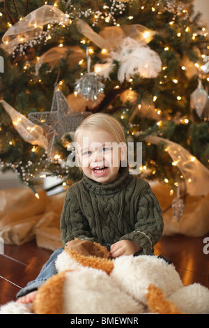 Jordan, Ontario, Canada; A Toddler Sitting Beside The Christmas Tree Laughing - Stock Photo