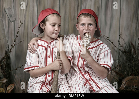 Two Boys Wearing Baseball Uniforms And One Is Eating An Ice Cream Cone - Stock Photo