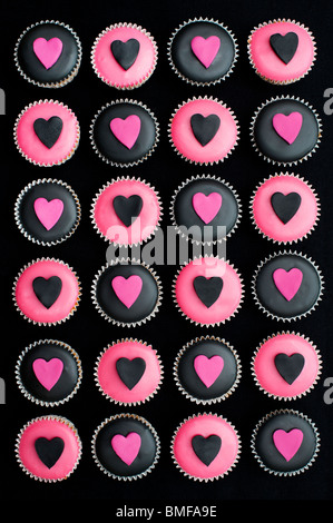 Mini cupcakes decorated with black and pink icing and heart shapes - Stockfoto