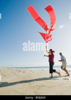 Couple flying kite on beach - Stock Photo