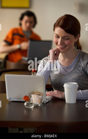 Woman working on laptop in coffee shop - Stock Photo