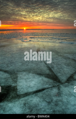 Sunrise across a frozen freshwater lake in Michigan, United States, North America with shifting ice sheets below - Stock Photo