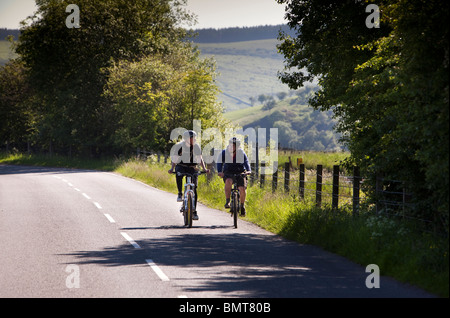 UK, England, Derbyshire, Edale, cyclists in Hope Valley cycling on empty road - Stock Photo