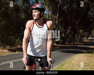 Young man cycling on road - Stock Photo