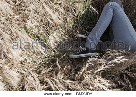Young woman lying in grassy field - Stock Photo