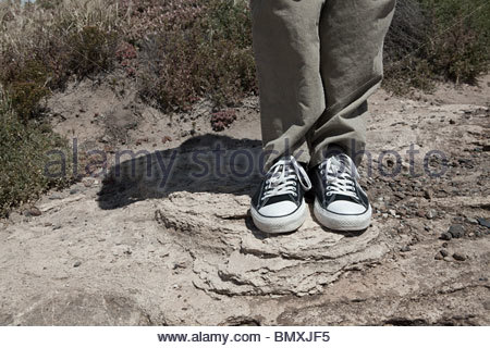 Young man standing on rocks, low section - Stock Photo
