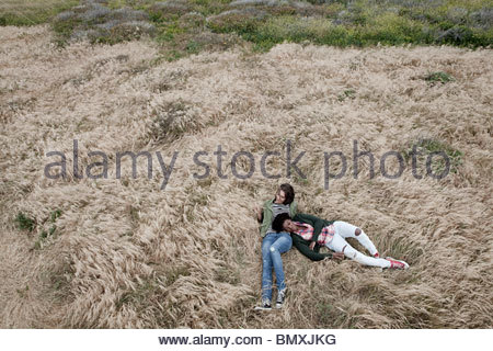 Young female friends lying in grassy field - Stock Photo