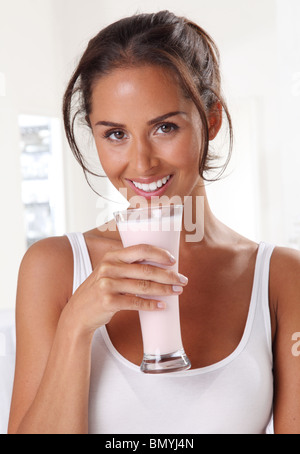WOMAN DRINKING STRAWBERRY MILKSHAKE OR SMOOTHIE - Stock Photo