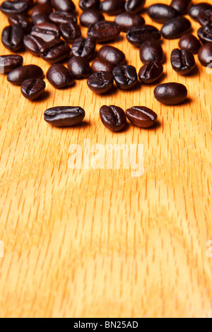 whole brown coffee beans on a wood background - Stock Photo