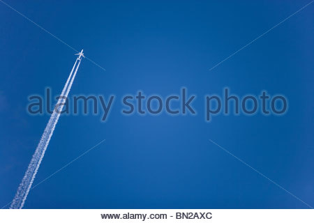 Airplane with contrail flying in clear, blue sky - Stock Photo