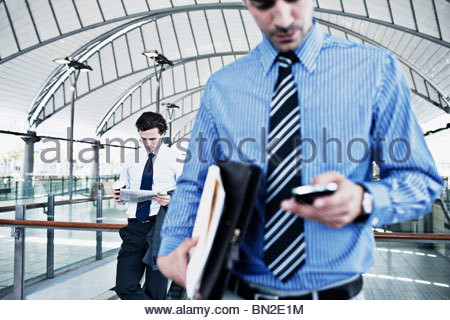 Businessman text messaging on cell phone - Stock Photo