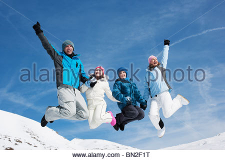 Family jumping in mid-air in snow - Stockfoto