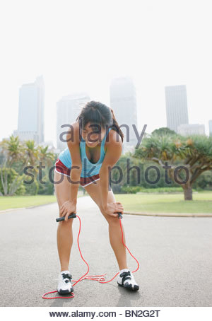 Woman resting after exercising with skipping rope - Stock Photo