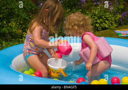 Two Young Female Children Playing In A Paddling pool - Stock Photo