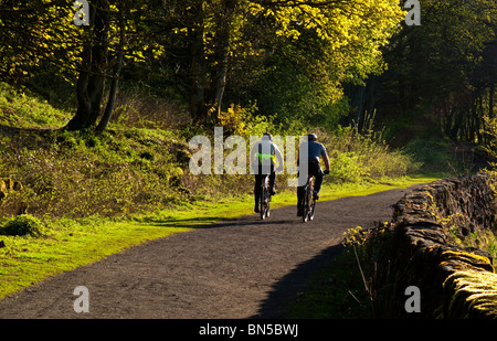 Pair of cyclists riding on the High Peak Trail near Wirksworth in the Derbyshire Dales part of the Peak District - Stock Photo