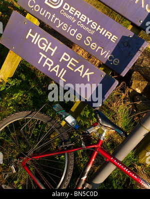 Cycle parked next to sign on the High Peak Trail near Wirksworth in the Derbyshire Dales part of the Peak District - Stock Photo