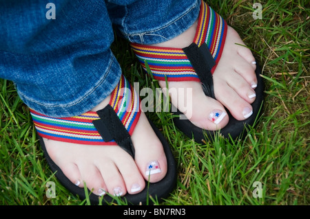 Pedicured toes show off red, white, and blue star decals in colorful flip flops on the 4th of July. - Stock Photo