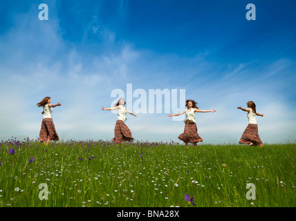Same young woman in different positions dancing on a beautiful green meadow - Stock Photo