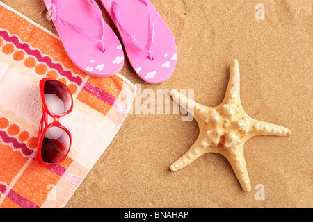 Towel, sandals, sunglasses and starfish at beach - Stock Photo