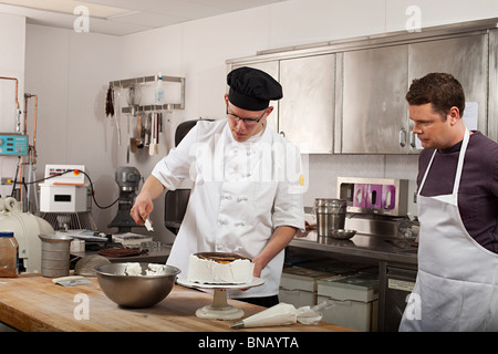 Chefs preparing food in commercial kitchen - Stock Photo