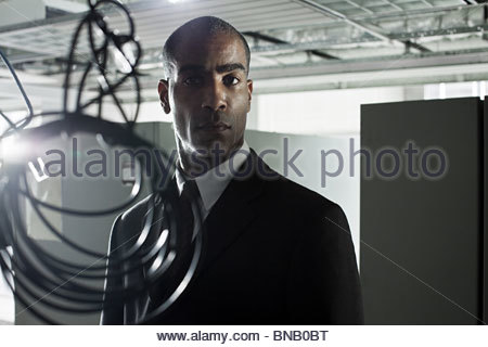 Businessman and cables in abandoned office - Stock Photo